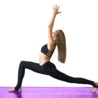 Young attractive woman practicing yoga, standing in Warrior one exercise, Virabhadrasana I pose, working out, wearing sportswear, black pants and top, indoor full length, studio background