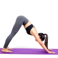 young asian woman doing yoga in Adho Mukha Svanasana or Downward-Facing Dog yoga pose on the mat isolated on white background, exercise fitness, sport training, healthy lifestyle and people concept